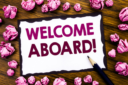 Hand writing text caption inspiration showing Welcome Aboard. Business concept for Greeting Join Member Written on sticky note paper, wooden background folded pink paper meaning thinking Banco de Imagens