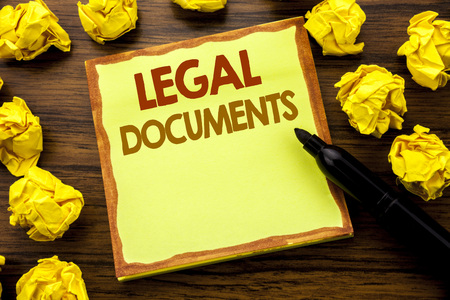 Hand writing text caption showing Legal Documents. Business concept for Contract Document Written on sticky note paper, wooden background marker folded yellow paper meaning thinking