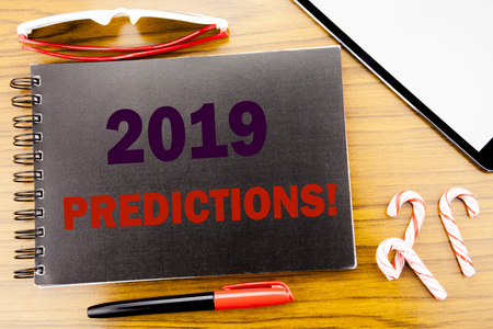 Handwriting Announcement text   2019 Predictions. Business concept for Forecast Predictive Written on notepad notebook book wooden background in office view with pencil marker and tablet