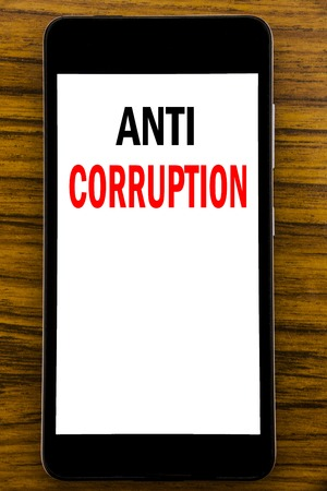 Handwriting Announcement text showing Anti Corruption. Business concept for Bribery Corrupt Text Written on mobile cellphone with wooden background with space on the table Foto de archivo