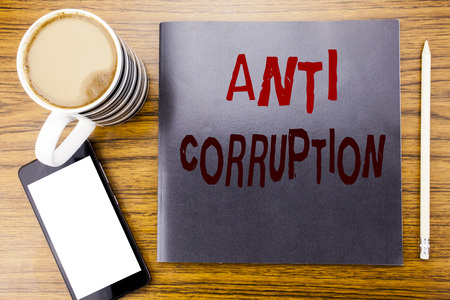 Handwriting Announcement text showing Anti Corruption. Business concept for Bribery Corrupt Text Written on notepad note paper, wooden wood background coffee pen and cellphone phone