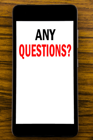 Handwriting Announcement text showing Any Questions. Business concept for Answer Help Question Written on mobile cellphone with wooden background with space on the table Stock Photo