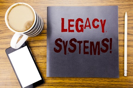 Handwriting Announcement text showing Legacy Systems. Business concept for Upgrade SOA Application Written on notepad note paper, wooden wood background coffee pen and cellphone phone
