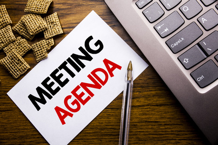 Handwriting Announcement text showing Meeting Agenda. Business concept for Business Schedule Plan written on sticky note paper on wooden background next to the laptop keyboard