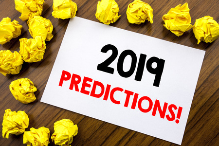 Handwritten text showing word 2019 Predictions. Business concept writing Forecast Predictive Written on sticky note, wooden background with space office view with folded yellow paper Stock Photo