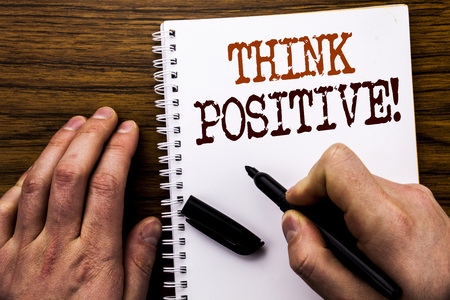 Handwritten text showing word Think Positive. Business concept for Positivity Attitude Written tablet laptop, wooden background with businessman hand, finger writing on notebook book. Reklamní fotografie