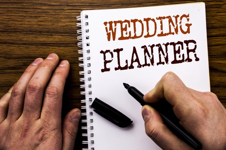 Handwritten text showing word Wedding Planner. Business concept for Marriage Preparation Written tablet laptop, wooden background with businessman hand, finger writing on notebook book. Stock Photo
