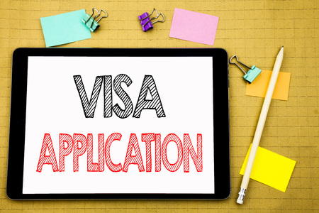 Word, writing Visa Application. Business concept for Passport Apply Written on laptop, wooden background with sticky note and pen