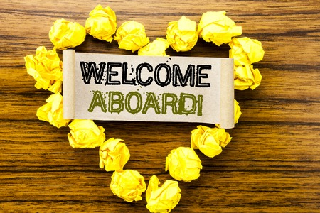 Word, writing Welcome Aboard. Business concept for Greeting Join Member written on sticky note paper on dark wooden background. With yellow folded paper heart meaning love or adoration.