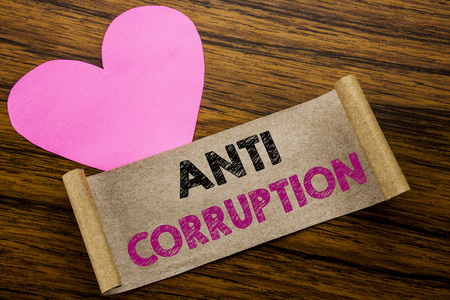 Writing text showing Anti Corruption. Business concept for Bribery Corrupt Text written on sticky note paper, wooden background. With pink heart meaning love adoration. Stock Photo