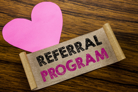Writing text showing Referral Program. Business concept for Refer Marketing  written on sticky note paper, wooden background. With pink heart meaning love adoration.