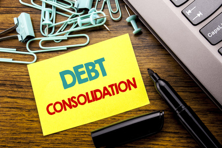 Handwriting Announcement text showing Debt Consolidation. Business concept for Money Loan Credit written on sticky note paper on wooden background next to the laptop keyboard With marker