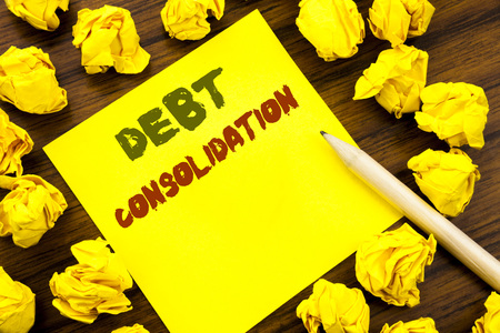 Word, writing Debt Consolidation. Business concept for Money Loan Credit Written on sticky note paper, wooden background folded yellow paper meaning thinking