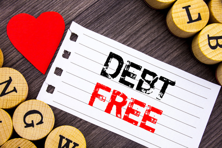 Handwriting text showing Debt Free. Conceptual photo Credit Money Financial Sign Freedom From Loan Mortage written tear note paper sticky note the wooden background with heart. Stock Photo