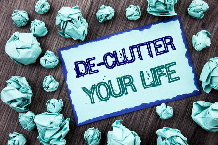Conceptual hand writing text showing De-Clutter Your Life. Concept meaning Free Less Chaos Fresh Clean Routine written Sticky note paper folded paper the wooden background.