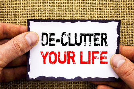 Writing text showing  De-Clutter Your Life. Concept meaning Free Less Chaos Fresh Clean Routine written Sticky Note Paper Holding Hand with Finger.