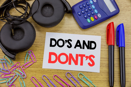 Writing text showing Do s And Do Not Donts. Business concept for Guide Allowed written on sticky note paper on wooden background. With calculator and pen marker and headphones