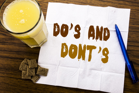 Handwriting Announcement text showing Do s And Do Not Donts. Business concept for Guide Allowed written on tissue paper on wooden background with pen and healthy juice in the restaurant Standard-Bild