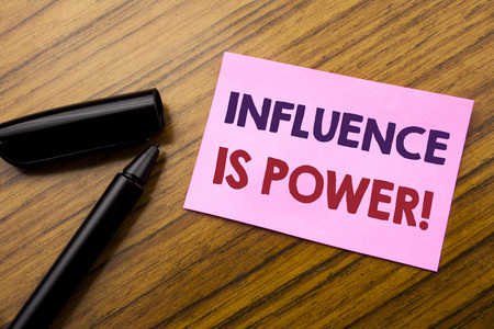 Word, writing Influence Is Power. Business concept for Persuasion Strategy Written on sticky note red paper, wooden background pen. Note stick on the desk.