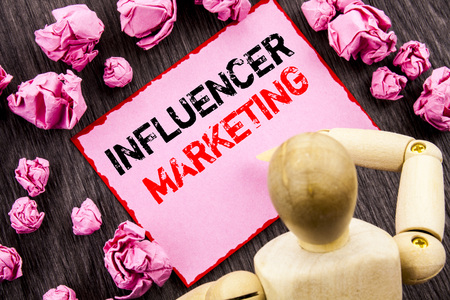 Conceptual hand text showing Influancer Marketing. Concept meaning Social Media Online Influence Strategy written Sticky Note Holding By Sculpture the wooden background.