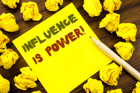 Word, writing Influence Is Power. Business concept for Persuasion Strategy Written on sticky note paper, wooden background folded yellow paper meaning thinking