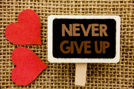 Conceptual hand text showing Never Give Up. Business photo showcasing Motivation Quote For Success Achievement Challenge written blackboard the textured background with Love Heart Stock Photo