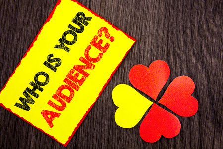 Text showing Who Is Your Audience Question. Business photo showcasing Customer Target Service Client Research written Sticky Note Paper with Love Heart Next to it the wooden background. Stok Fotoğraf