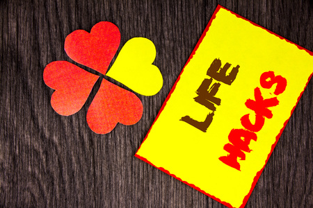 Text sign showing Life Hacks. Business concept for Solution Hacking Hack Trick To Help Efficiency written Sticky Note Paper with Love Heart Next to it the wooden background Stock Photo