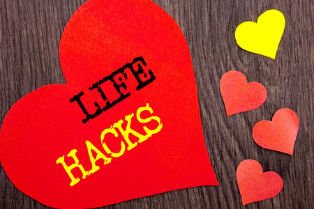Handwriting Announcement text showing Life Hacks. Concept meaning Solution Hacking Hack Trick To Help Efficiency written Heart Love the wooden background. Stock Photo