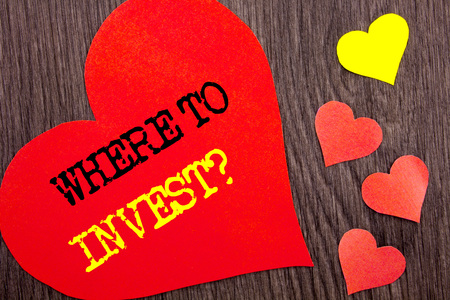 Handwriting Announcement text showing Where To Invest Question. Concept meaning Financial Income Investing Plan Advice Wealth written Heart Love the wooden background.