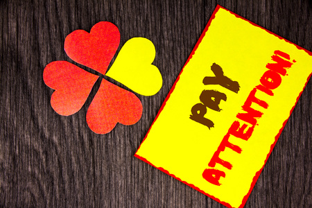 Text sign showing Pay Attention. Business concept for Be Careful Beware Mindful Alarm written Sticky Note Paper with Love Heart Next to it the wooden background