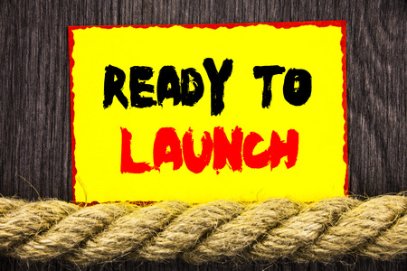 Handwritten text sign showing Ready To Launch. Conceptual photo Prepare New Product Promotion Start Release written Sticky note next to the rope the wooden background.