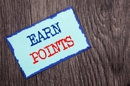 Writing text showing  Earn Points. Business photo showcasing Loyalty Reward Benefit Program For Earning Customer Point written Blue Sticky Note Paper the wooden background. Foto de archivo