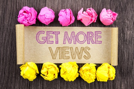 Writing text  Get More Views. Concept meaning More Traffic Leads Online Page Promotion Popularity Traffic written sticky note paper with folded paper yellow and pink the wooden background.