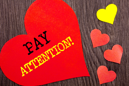 Handwriting Announcement text showing Pay Attention. Concept meaning Be Careful Beware Mindful Alarm written Heart Love the wooden background. Stock Photo