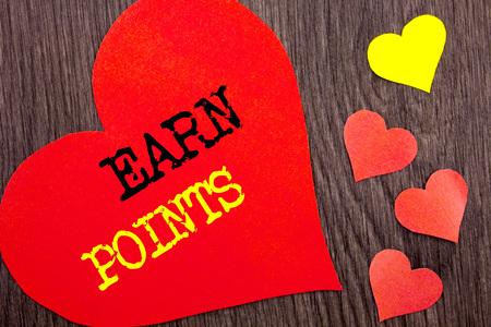 Handschrift-Ansagetext, der Verdienen Sie Punkte zeigt. Konzeptbedeutungs-Loyalitäts-Belohnungs-Nutzen-Programm für das Erwerben des Kundenpunktes geschriebenes Herz-Liebe der hölzerne Hintergrund. Standard-Bild