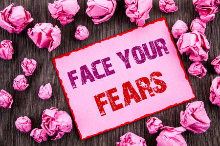 Handwriting text showing Face Your Fears. Business photo showcasing Challenge Fear Fourage Confidence Brave Bravery written Pink Sticky Note Paper Folded Paper wooden background Stock Photo