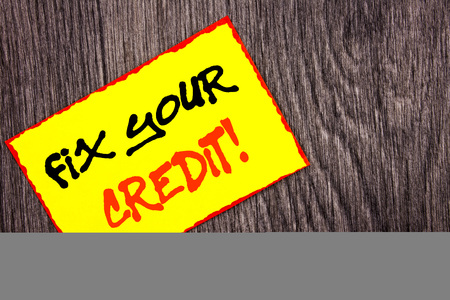 Conceptual hand writing text showing Fix Your Credit. Concept meaning Bad Score Rating Avice Fix Improvement Repair written Yellow Sticky Note Paper the wooden background. Stock Photo