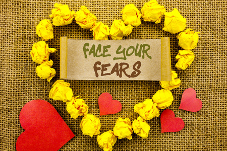 Handwriting Announcement text showing Face Your Fears. Concept meaning Challenge Fear Fourage Confidence Brave Bravery written Sticky Note Paper With Heart the textured background Stock Photo