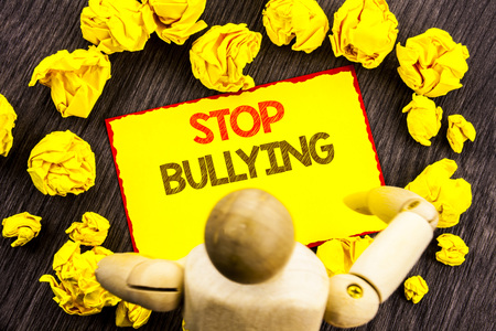 Writing text showing  Stop Bullying. Business photo showcasing Awareness Problem About Violence Abuse Bully Problem written Sticky Note Holding By Sculpture the wooden background