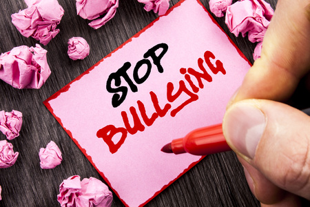 Text sign Stop Bullying. Business concept for Awareness Problem About Violence Abuse Bully Problem written Pin Sticky Note Paper Folded Paper wooden background Man Holding Marker Hand Stock Photo - 96902247