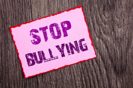 Handwriting Announcement text showing Stop Bullying. Conceptual photo Awareness Problem About Violence Abuse Bully Problem written Pink Sticky Note Paper the wooden background. Archivio Fotografico