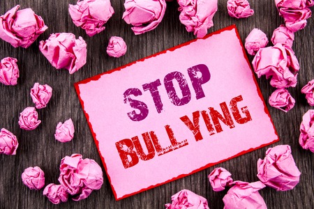 Handwriting text showing Stop Bullying. Business photo showcasing Awareness Problem About Violence Abuse Bully Problem written Pink Sticky Note Paper Folded Paper wooden background