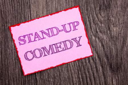 Handwriting Announcement text showing Stand Up Comedy. Conceptual photo Entertainment Club Fun Show Comedian Night written Pink Sticky Note Paper the wooden background.