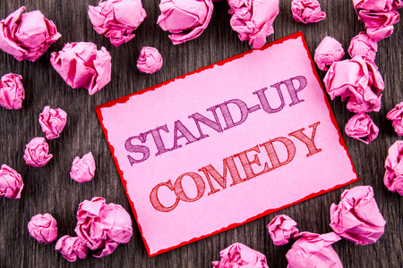 Handwriting text showing Stand Up Comedy. Business photo showcasing Entertainment Club Fun Show Comedian Night written Pink Sticky Note Paper Folded Paper wooden background 写真素材