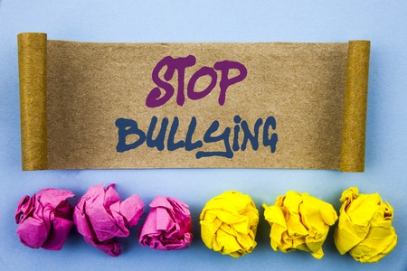 Handwriting text showing Stop Bullying. Concept meaning Awareness Problem About Violence Abuse Bully Problem written tear sticky note Paper the blue background Folded paper