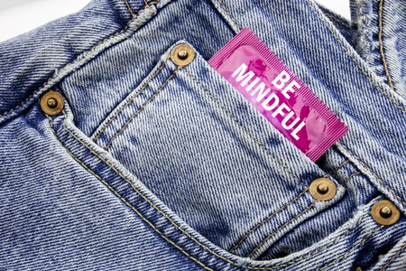 Handwriting Announcement text showing Be Mindful. Business concept for Mindfulness Healthy Spirit Written on condom pack put in small pocket to pants jeans. Stock Photo