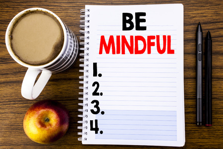 Handwritten text showing Be Mindful. Business concept for Mindfulness Healthy Spirit written on notepad paper on the wood structure background background.