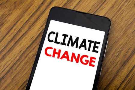 Word, writing handwriting Climate Change. Business concept for Global Planet Warming Written on mobile phone, wooden background with copy space.