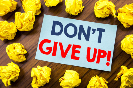 Conceptual hand writing text inspiration showing Don t Give Up. Business concept for Motivation Determination, written on sticky note paper the wooden background with folded yellow paper